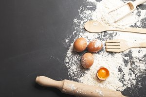Background of eggs, wooden spoon with flour and cookware on black background. Copy space.