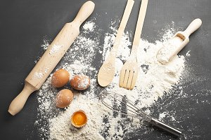 Background of eggs, wooden spoon with flour and cookware on black background.