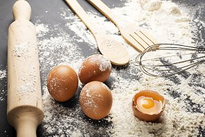 Background of eggs, wooden spoon with flour and cookware on black background. Horizontal studio shot.