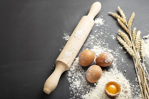 Background of eggs over flour together with wheat flower and wooden roll. Copy space.
