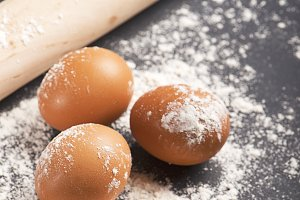 Eggs on flour next to wooden roller on black wooden table. Vertical studio shot.