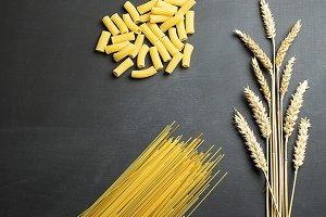 Wheat flower next to pasta on black background.