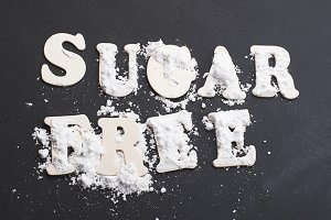 Sugar free written with wooden letters on black background.