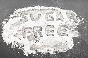 Sugar free written on in sugar on black background.