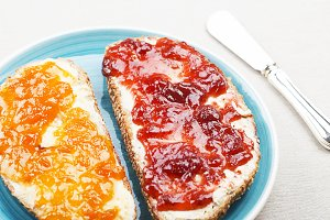 Close-up of two toasts with strawberry jam and peach on blue plate.