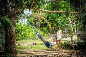 Portrait of a happy young romantic couple in a hammock during their vacation on the tropical island Bali, Indonesia. Love scene. Asia. Girl is staying near her boyfriend.