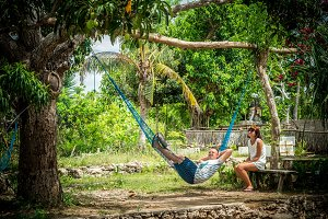Portrait of a happy young romantic couple in a hammock during their vacation on the tropical island Bali, Indonesia. Love scene. Asia. Girl is sitting near her boyfriend.