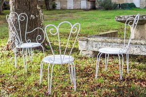Decorative vintage metal white chairs furniture in a garden