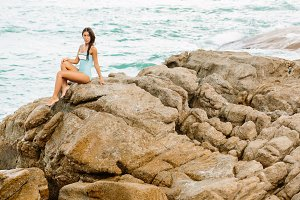 Beautiful girl sit at stone beach.