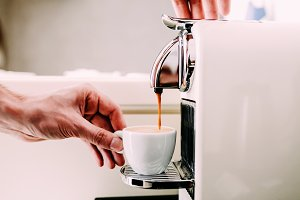 The man is holding a white cup. Close-up, coffee preparation by a professional coffee machine