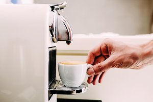Close up of hand of a barista making coffee using a coffee machine. Man's hand with a cup of fresh coffee with foam