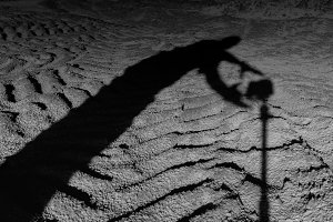 Square black and white scary man shadow taking photo camera on t