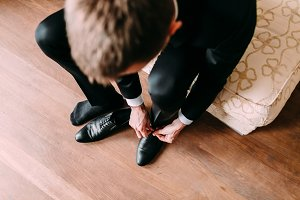 Business man tying shoe laces on the floor. Groom getting ready in the morning before the wedding