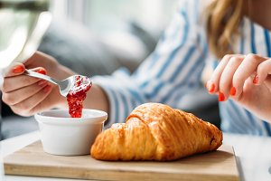 Woman eating croissant with jam