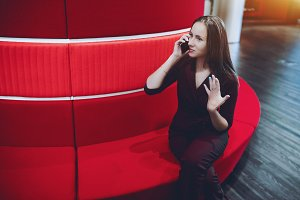 Businesswoman on red office sofa