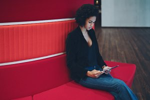 Black girl on red sofa in office