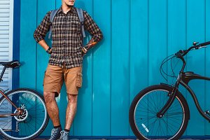 Unrecognizable young man traveler with a backpack stands next to bicycles near blue wall. Rest during the trip, halt