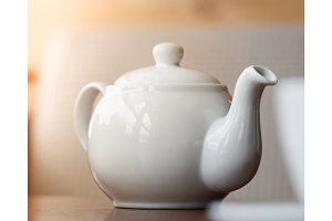 Close-up of white teapot on the table.