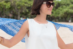 Outdoor summer portrait of young pretty woman in white dress with sunglasses and silk scarf near the ocean at tropical beach, enjoy her freedom and fresh air, stylish look.