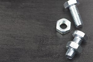 Background of nuts and bolts on black background. Copy space.