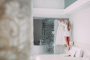 Bride in silk robe takes her dress from the cornice. Morning preparation before wedding