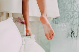 Bride takes her dress from the cornice. Wedding. Slender legs of a beautiful girl