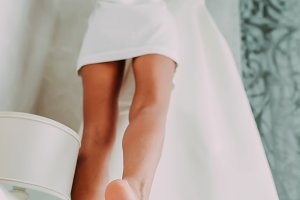 Bride in silk robe takes her dress from the cornice. Wedding. Slender legs of a beautiful girl