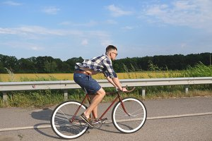 Young handsome man riding at vintage bicycle in the country road. Sporty guy cycling at the track. Male cyclist riding fixed gear bike at highway. Healthy active lifestyle Slow motion