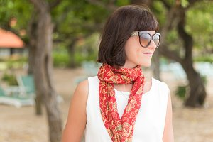 Beauty portrait of sexy brunette woman in white dress on the beach with colorful silk scarf and sunglasses. Cruise summer fashion. Bali, Indonesia.