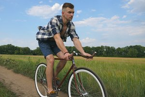 Young man riding vintage bicycle at the rural road over field. Sporty guy cycling along country trail outdoor. Male cyclist riding bike in the countryside. Healthy active lifestyle Slow motion