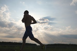 Silhouette of muscular man jogging in the country road at sunset. Male jogger training for marathon run outdoor. Athlete exercising and running against blue sky. Sport and active lifestyle Slow motion