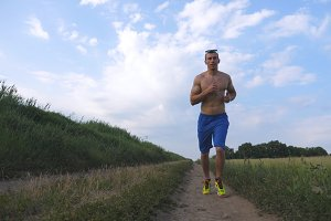 Muscular man running at country road. Young athletic guy jogging at rural trail over the field. Male sportsman training at nature. Runner exercising outdoor. Slow motion Healthy active lifestyle