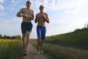 Two muscular men running outdoors. Young athletic guys jogging over the field. Male sportsmans training together at nature. Friends exercising outside. Slow motion Healthy active workout lifestyle