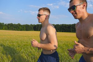 Two muscular men running outdoors. Young athletic guys jogging over the field. Male sportsmans training together at nature. Friends exercising outside. Slow motion Healthy active lifestyle