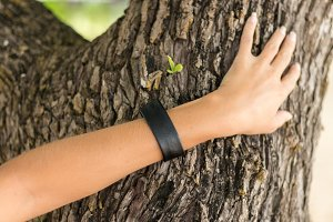Young woman hand with handmade skin bracelet on the tree background.