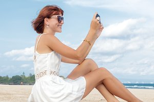 Sexy young woman using smartphone in hand on the beach of tropical Bali island. Beatiful view.