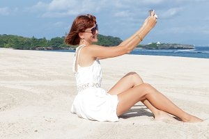 Beautiful sexy young woman doing selfie and smiling on the beach of tropical Bali island. Ocean view.