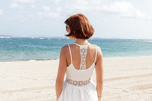 back view of young woman in white dress on the tropical beach of Bali island, Indonesia. Ocean view.