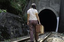 Woman and vintage suitcase on railwa