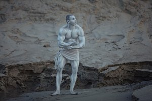 Male bodybuilder poses as a statue.