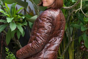 Beautiful lady dressed a luxury snaskin python coat and sunglasses outdoors. Bali island garden outdoors.