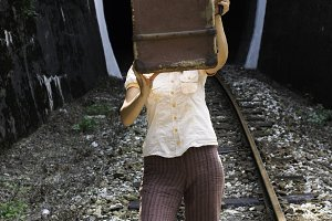 Woman and vintage suitcase on railwa