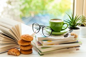 Coffee cup, open book, glasses