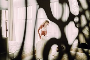 Sexual bride in white lingerie is putting on her white wedding dress.
