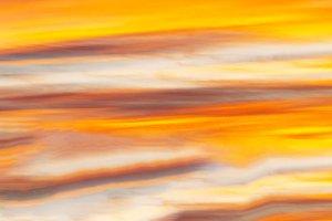 Horizontal vibrant orange sunset cloudscape background backdrop