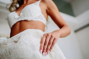 Sexual bride in white lace lingerie is putting on her white wedding dress. Morning preparation