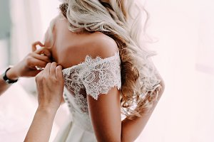 Gorgeous, blonde bride in white luxury dress is getting ready for wedding. Morning preparations. Woman putting on dress.