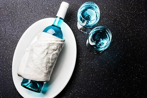 Bottle and two glasses of trendy blue wine. Spanish blue wine chardonnay on black background. Fancy wine, top view