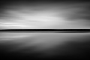 Horizontal black and white sunset horizon smooth lake background