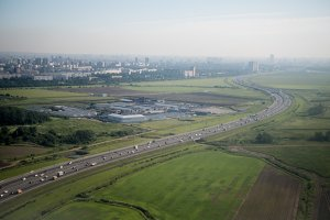 Panorama of highway with cars and modern city, aerial view